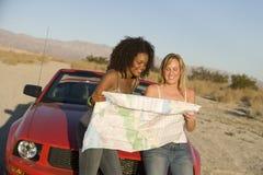 Amis regardant la carte tout en se penchant sur la voiture Photographie stock libre de droits