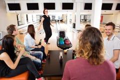Amis regardant la femme dans le club de bowling Photographie stock