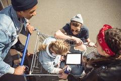 Amis regardant la fille blonde s'asseyant dans le caddie avec le comprimé numérique Image stock