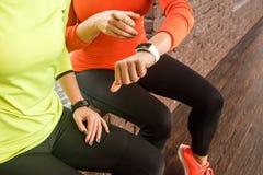 Amis regardant la montre ou le traqueur futée de forme physique Photographie stock libre de droits