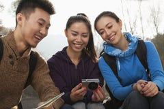 Amis regardant la photo sur l'écran de l'appareil photo numérique Image libre de droits