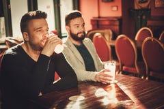 Amis regardant la TV et buvant de la bière pression dans le bar Photos stock
