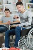 2 amis regardant la TV et buvant la soude une handicapée Photos libres de droits