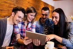 Amis regardant le comprimé numérique dans le restaurant Photo libre de droits