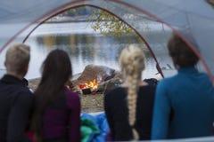 Amis regardant le feu de camp de la tente Image libre de droits
