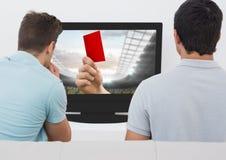 Amis regardant le match de football à la télévision Photographie stock libre de droits