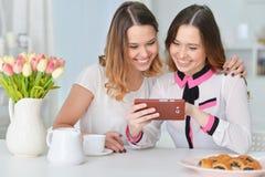 Amis regardant le smartphone Photos libres de droits