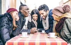 Amis regardant le smartphone dans une barre Photographie stock