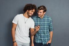 Amis regardant le téléphone Photos libres de droits