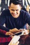 Amis regardant le téléphone intelligent tout en se reposant en café Image stock