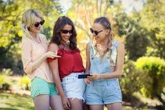 Amis regardant le téléphone portable Photographie stock libre de droits