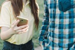 Amis regardant le téléphone portable dehors Images stock