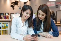 Amis regardant le téléphone portable ensemble dans le café Photo stock