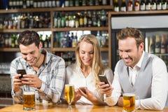 Amis regardant les téléphones intelligents Image libre de droits
