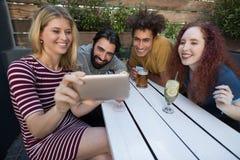 Amis regardant leurs photos au téléphone portable dans la barre Photo stock