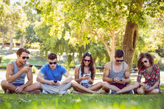 Amis regardant leurs smartphones Photos libres de droits