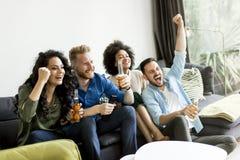 Amis regardant TV, cidre potable et ayant l'amusement dans la chambre Photos stock
