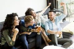 Amis regardant TV, cidre potable et ayant l'amusement dans la chambre Photos libres de droits
