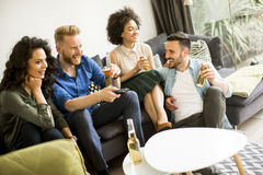 Amis regardant TV, cidre potable et ayant l'amusement dans la chambre Photographie stock