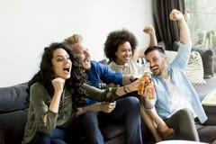 Amis regardant TV, cidre potable et ayant l'amusement dans la chambre Images libres de droits
