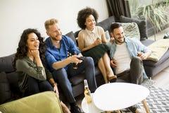 Amis regardant TV, cidre potable et ayant l'amusement dans la chambre Photo stock