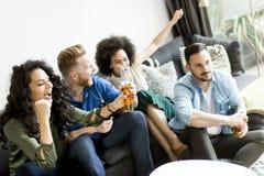 Amis regardant TV, cidre potable et ayant l'amusement dans la chambre Image stock