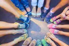Amis remontant leurs pieds dans un signe de l'unité et du teamw Photo stock