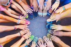 Amis remontant leurs pieds et mains dans un signe de l'unité Photographie stock libre de droits