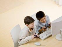 Amis retenant des contrôleurs de jeu vidéo ayant l'amusement Images libres de droits