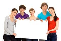 Amis retenant un panneau blanc Image stock