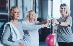 Amis retirés occupés positifs joignant la bouteille de l'eau après la formation Photographie stock libre de droits