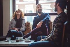 Amis riant dans un café tout en buvant du café Image stock