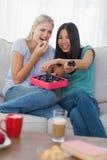Amis riant de la TV et partageant la boîte de chocolats Image stock