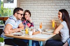 Amis riant du déjeuner Photographie stock libre de droits