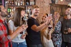 Amis riant ensemble tout en se tenant boit Photographie stock