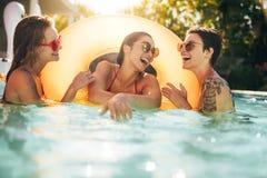 Amis riant et appréciant dans la piscine Photo libre de droits