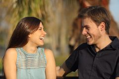 Amis riant et prenant une conversation en parc Photo stock
