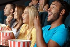Amis riant pendant un film Images stock