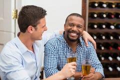 Amis riant tout en ayant la bière Photos libres de droits