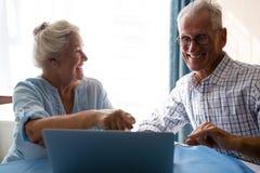 Amis riant tout en regardant l'ordinateur portable Photographie stock libre de droits