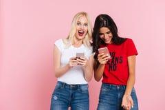 Amis riants à l'aide des smartphones et sourire d'isolement Photo stock