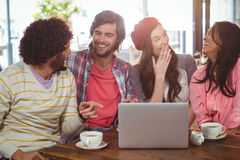 Amis riants appréciant le café avec l'ordinateur portable Photo libre de droits