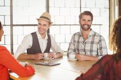 Amis riants ayant le café ensemble Image libre de droits