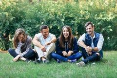 Amis riants drôles s'asseyant sur l'herbe avec les jambes croisées Image libre de droits