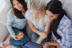 Amis riants employant le comprimé numérique ensemble et manger le biscuit Images stock