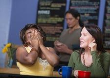 Amis riants en café Images libres de droits