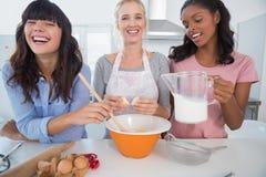 Amis riants faisant la pâtisserie ensemble Photo stock
