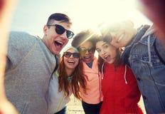 Amis riants heureux prenant le selfie Photo stock