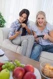 Amis riants jouant des jeux vidéo Images stock