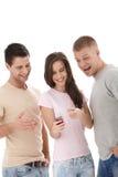 Amis riants regardant le téléphone portable Photos libres de droits